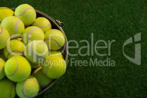 High angle view of fluorescent tennis balls in bucket