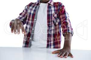 Boy pretending to work on an invisible object against white background