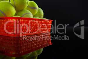 Pile of fluorescent yellow tennis balls in red plastic basket with reflection