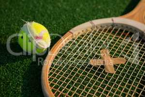 Close up of tennis ball and racket with bandage
