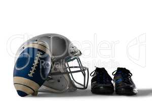 Close up of America football and helmet by sports shoes