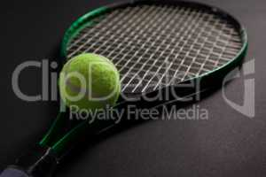 Close up of fluorescent yellow tennis racket and ball