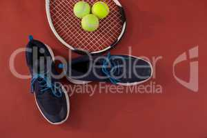 Overhead view of blue sports shoes by tennis racket and balls