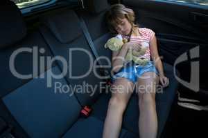 Teenage girl sleeping in the back seat of car