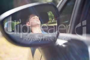 Reflection of teenage boy in wing mirror sleeping in car