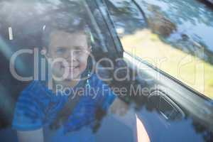 Teenage boy sitting in the front seat of car