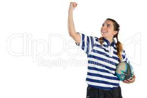 Happy female athlete holding rugby ball while standing with clenching fist