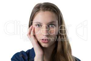 Confused teenage girl with hand on face