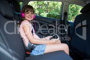 Teenage girl in headphones using digital tablet in the back seat of car