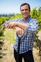 Portrait of smiling vintner standing with gardening equipment