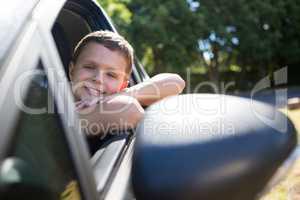 Teenage boy sitting in the back seat of car