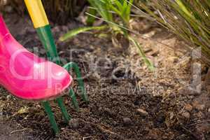 Close-up of woman loosening soil with garden fork