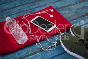High angle view of water bottle with mobile phone and in-ear headphones on napkin by sports shoes
