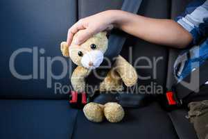 Teenage boy sitting with teddy bear in the back seat of car