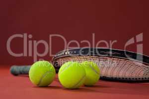 Close up of tennis racket on balls