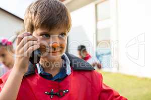 Boy with face paint using walkie talkie while looking away