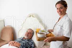 Female doctor serving food to senior patient relaxing on bed in retirement home