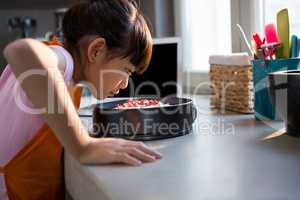Girl looking at cake in container