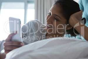 Smiling woman using phone while resting on bed