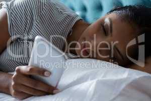 Relaxed woman using phone on bed