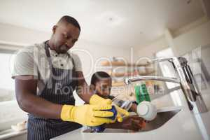 Father and son cleaning utensils in kitchen
