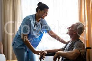Female doctor interacting with senior man in nursing home