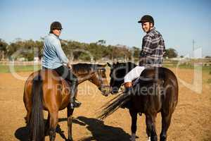 Two male friends riding horse in the ranch