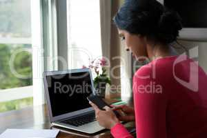 Young woman with laptop using phone