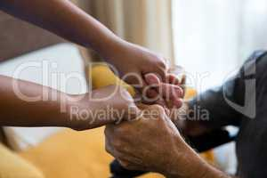 Female doctor and senior man holding hands in nursing home