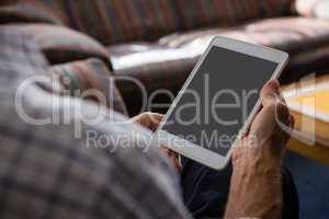 Hands of senior man using tablet computer while sitting in nursing home