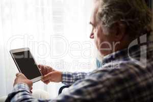 Side view of senior man using digital tablet in nursing home