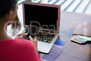 Woman with laptop using phone