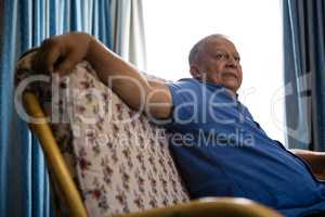 Senior man looking away while relaxing on sofa at retirement home