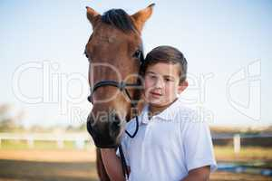 Rider boy caressing a horse in the ranch
