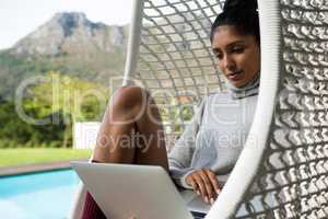 Woman using laptop on swing chair