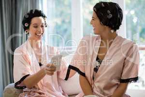 Bride and her friend using mobile phone