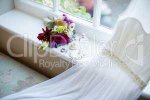 Bouquet of flower and wedding dress kept on window sill