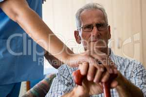 Female doctor standing by senior man sititng on sofa in retirement home
