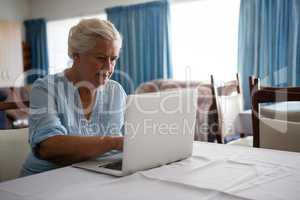 Senior woman using laptop while sitting in nursing home