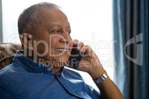 Smiling senior man talking on mobile phone in nursing home