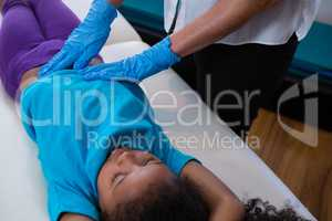 Physiotherapist giving abdomen massage to girl patient