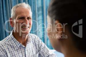senior man interactin with female doctor in retirement home