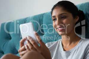 Smiling woman using phone in bedroom