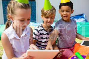 Children using digital tablet during birthday party