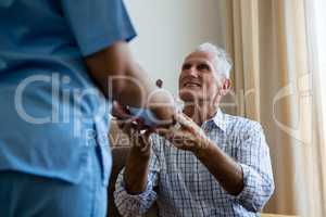 Female doctor serving food to senior man at retirement home
