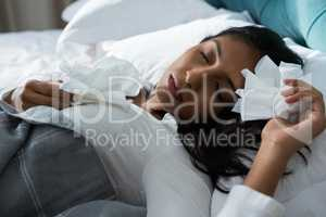 Sick woman with tissues sleeping on bed