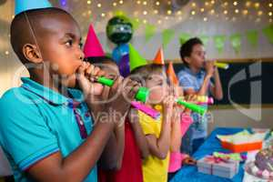 Children blowing party horns