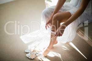 Bride wearing stockings in living room