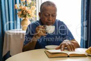 Senior man having drink while reading book in nursing home
