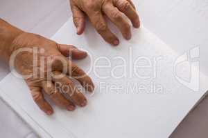 Cropped hands of senior woman reading braille in nursing home